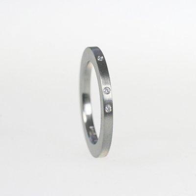 Ring in Edelstahl, 2mm breit, 3 Brillanten à 0,01ct, unregelmäßig gefasst. mattierte Oberfläche